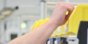 Ein Mitarbeiter greift mit Pick-by-Light ein Teil aus einem Behälter zur Kommissionierung des Auftrags.